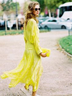 A beautiful yellow lace maxi dress is worn with unexpected sneakers