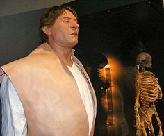 A photo of a reconstruction of a sailor standing next to a skeleton - bad shoulders