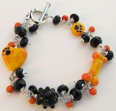 Jet black crystals and artisan lampwork 3D heart, dog bone, and paw print beads in sunset orange combined for a one of a kind dog lover bling bracelet.  Handmade by Sue at For Love of a Dog