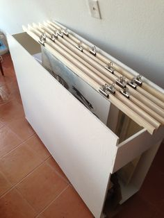 Mobile art storage unit. Basla strips with binder clips to hold art, inside a smooth pine wood frame painted and left open on the sides for sir circulation