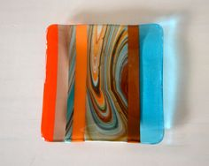 Shades of the southwest are the lovely turquoise, orange, tan, brown blends all swirled together.    Slumped in a sushi style dish. It measures approx 5.25 square- use it in the kitchen as a spoon rest- sponge rest- it adds so much color. This dish can be a jewelry tray, candy dish, soap dish...key dish..and on and on. If you would like silicone feet for it, just add that in the notes when you purchase.    My items are designed, cut and fused in my home studio. The dish is heavy and durable…