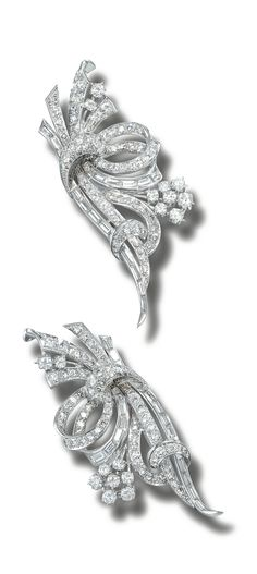 DIAMOND DOUBLE-CLIP BROOCH, CIRCA 1960.  Each designed as stylised entwined ribbon, set throughout with brilliant-, circular- and single-cut and baguette diamonds, mounted in platinum.