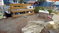 Mud Kitchen with bench and plenty of room for muddy play. Large boulders are incorporated in the messy play.