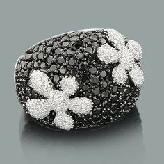 This Ladies Black and White Diamond Flower Cocktail Ring in 18K Gold weighs approximately 11 grams and showcases 3.25 carats of sparkling round diamonds. Featuring a unique design and a highly polished gold finish, this ladies diamond ring is available in 18K white, yellow and rose gold.