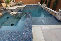 Classic pool design featuring mosaic tile surrounded spa, tanning ledge, raised stone wall with planters By-Outdoor Signature in Argyle, TX