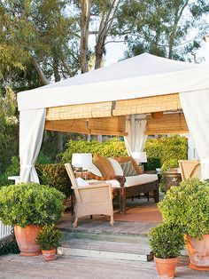 Blend into Your Surroundings Weather-resistant fabric panels provide a romantic backdrop to this outdoor room, hiding the tent's structure and giving the space an intimate, enclosed feel. An assortment of potted plants blends the room with the yard.