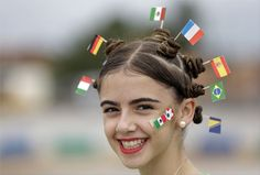 A fan donning miniature national flags representing Italy, Germany, Mexico, the Netherlands, Spain, Brazil and Bosnia in her hair smiles, prior to the group A World Cup soccer match between Brazil and Mexico at the Arena Castelao in Fortaleza, Brazil, Tuesday, June 17, 2014. (AP Photo/Themba Hadebe)