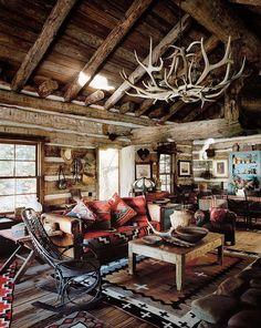 Knusse chalet woonkamer met lamp van rendiergewei. Hoe rustiek wil je het hebben?