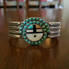 Ca.1940s Zuni inlay Sunface cuff. Handmade from sterling silver, natural turquoise, spiny oyster, jet, and mother of pearl. Measurements are…