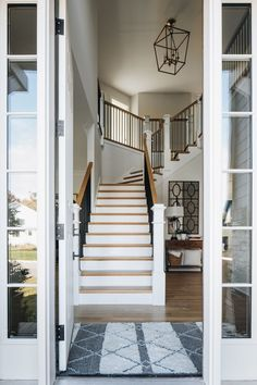 open front door showing a staircase up to a second story landing. to the right is a hallway with a wood entry table, lamp, and mirror. Country Wall Mirrors, Benjamin Moore Classic Gray, Oak Floating Shelves, Grey Siding, Room For Improvement, Dark House, Modern Style Homes, White Countertops, Visual Comfort