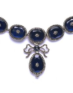 Necklace of blue foiled paste gems with a pyrite (commonly known as marcasite) border, set in silvered copper and hung with a pendant, possibly France, about 1810-40. Length: 32.0 cm, Height: 16.6 cm when fastened, Width: 12 cm when fastened, Depth: 1 cm.
