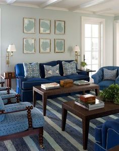 Navy blue sofa against a very light blue wall.