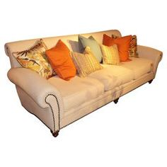 """Nailhead-trimmed sofa with rolled arms and turned wood legs.  Product: SofaConstruction Material: Solid wood frame and down blend fillColor: CreamFeatures:  Brass nailhead trimIncludes two 23"""" x 23"""" pillows and one 23"""" x 13"""" pillow"""
