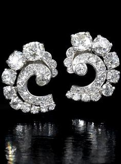 A pair of diamond earrings, by Cartier, circa 1930 Of scroll design, each set throughout with old brilliant and single-cut diamonds, mounted in platinum, diamonds approximately 4.00 carats total, each signed Cartier London, length 1.9cm