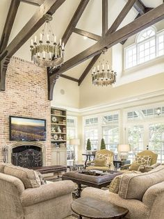 Seriously in love with this living room- the exposed beam ceiling, the rustic chandeliers, the brick fireplace, everything!