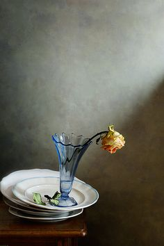 http://nikolay-panov.artistwebsites.com/products/faded-rose-nikolay-panov-art-print.html • Minimalistic still life with single faded rose in blue vase staying on white plates.