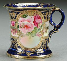 A NIPPON COBALT DECORATED SHAVING MUG CIRCA 1900 WITH HAND PAINTED ROSES IN GILT CARTOUCHE.