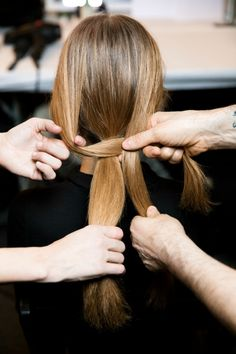 First, he prepped the model's hair by blow-drying it with Aveda Thickening Tonic. Then he created a center part and divided her hair into three sections, like this.
