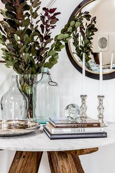Greenery, glass, mirror, books, and candles with stone and distressed wood round table for a well layered vignette. Entryway Round Table, Foyer Table Decor, Entry Tables, Table Decorations, Coastal Farmhouse, Farmhouse Decor, Modern Farmhouse, Farmhouse Plans, Coastal Cottage