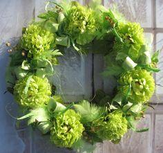 Zelenozelený III Jarní věneček o průměru 33 cm, laděný do zelené barvy. Latkové květiny, peří, mašle.