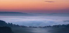https://flic.kr/p/HsPk51 | Am Rande der Welt | Ein paar Häuschen schlummerten an diesem Morgen noch vor sich hin, als dicker Nebel an ihnen vorbeizog. Hier und da ein paar Straßenlaternen. Das Örtchen wirkt vor der mächtigen Nebeldecke regelrecht winzig. Die Färbung des Himmels macht dieses Bild gleich noch dramatischer und gibt einen hübschen Kontrast zu den kühlen Farben im Vordergrund. In der Ferne sah ich diese kleine Szene und ich hoffe, dass dieses Bild die Stimmung gut transportieren…
