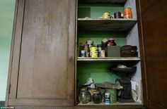 The wooden cupboard in the kitchen suffers from woodworm but still bears groceries bought decades ago