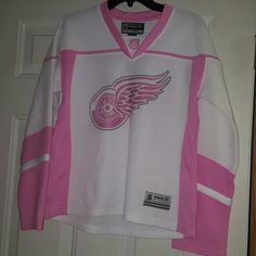 Womens Pink&White Red Wings Jersey bundle!! Authentic reebok Pink&White womens jersey, no name on back Was the limited edition back in 2009. Once I got my ozzy jersey, Held onto it but hardly worn . Minimal Imperfections shown in picture. 2 small light stains on lower  front and small snag on right lower sleeve. Pink Detroit Tigers bear  key chain and a pink and black Detroit Lions medium bag.  Bag has normal signs of wear on handle. Handle is adjustable Jersey says large, I feel fits small…
