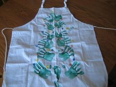 A Christmas tree apron with hand and feet prints.