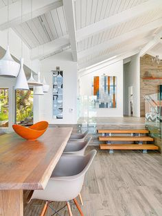Soaring white-washed ceilings, simulated wood porcelain tile planked floors and pendant lighting strung at various lengths. l Coastal Living Rooms l www.DreamBuildersOBX.com