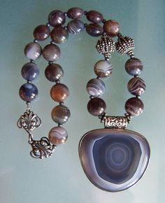An incredible large slice of Botswana agate beautifully set in a Sterling Silver bezel. Strung with 12mm Botswana puff lentil beads. Necklace measures 15.75″. with a hook and eye closure. Pendant measures 43mm x 49mm