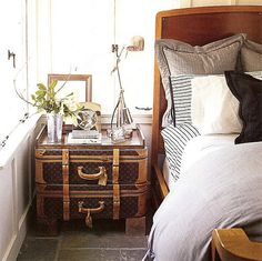 Stacked vintage luggage is repurposed as a lovely bedside table.