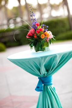 Bring color to cocktail hour with turquoise cocktail table linens accented by a cyan sash. Add a rainbow of brightly colored flowers for an eye-catching centerpiece. #CocktailHour #CocktailTables