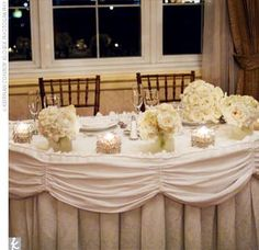 Penny chose to have three different centerpieces in three distinct heights. One had votive candles suspended from branches with crystals dripping from each candle. Medium-height centerpieces featured three brown pillar candles in three different heights, ...