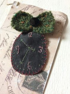 Hand stitched clock brooch with green knitted bow