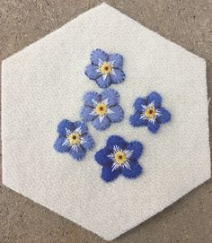 Forget Me Nots--Outline-backstitch3 strands variegated floss; Straight Stitch to divide petals #8 Perle cotton; Center- Algerian eye #12 Perle cotton, Colonial knot #8 Perle cotton; Around center straight stitches 2 strands floss