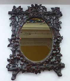 This is a stunning late Victorian hand carved mirror frame. It is probably German in origin, carved in the Black Forest style. The mirror probably was designed as a table top one - with a stand at the back, but has recently been converted to hang on the wall. This mirror and Black Forest frame is just exquisite - and as you can see from my photographs the carving is certainly most superior in detail and craft. The mirror frame is tromphe loeil and carved from one piece of wood to resemble a…