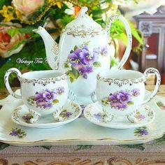 Two  three legged  cups saucer and tea pot decorated with violets, classic