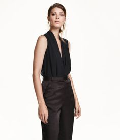 Sleeveless bodysuit with chiffon bodice and jersey lower section. Low-cut V-neck, pleats at front, concealed zip at back, and hook-and-eye fasteners at back of neck. Unlined.