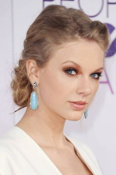 Gorgeous eye makeup on Taylor Swift. The blue of her earrings and the coral eye shadow make her eyes pop.