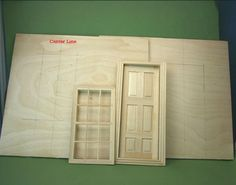Center lines for a dolls house window and door marked on plywood sides of a 1:12 scale roombox.