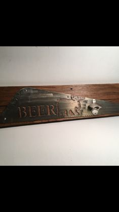 """BEER"".  Hand cut from a hand saw blade.  Mounted on a pallet board plaque.  Bottle opener attached."