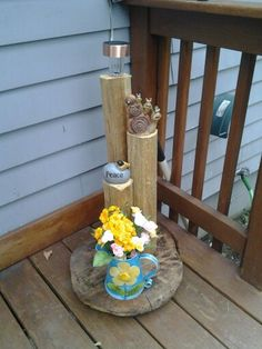 I used a slice of tree trunk 1 landscape timber and different items from the dollar store the light is from Wal-Mart taken apart . Cut the timber in different lengths I used 2/1/2  1 1/2 and 1 use screws to hold the timbers in place drill hole in top of tallest post and place light add flowers