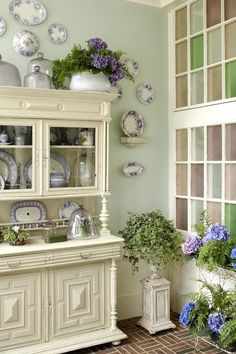 My style!  Love the white cabinet with greenery against the colored glass.
