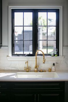 White window frames, black sashes and mullions, brass sink faucet