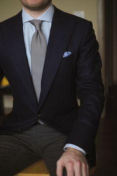 Comprar ropa de este look: https://lookastic.mx/moda-hombre/looks/blazer-camisa-de-vestir-pantalon-de-vestir/18621 — Camisa de Vestir de Rayas Verticales Gris — Corbata Gris — Pañuelo de Bolsillo Estampado Azul — Blazer Negro — Pantalón de Vestir de Lana Gris Oscuro
