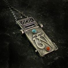 Large, mysterious pendant-syllable Om Tibetan amulet, made from scratch by hand the traditional goldsmithing techniques, silver pr. 925. stones - turquoise and coral. Mobile - dangling longer element (hinged). Postarzone and burnished silver. The length of approx. 5.5 cm, width approx. 3 cm. Weight: 17 gr. Chain length - 65 cm.