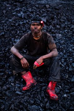 20-year-old Anil Basnet sits for a portrait above the coal mine where he works on April 13, 2011 in Jiantia Hills, India. Many workers leave homes in neighboring states, and countries, like Bangladesh and Nepal, hoping to escape poverty and improve their quality of life. (Daniel Berehulak/Getty Images)