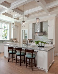 Beach style kitchen with a gray island countertop, high coffered ceiling, and pendant lights.