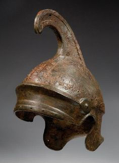GREEK IRON HELMET OF ATTIC TYPE of several sections riveted in place, the cap with a raised brow band, a carinated band above, each end terminating in a molded shield with a pointed center, a raised band encircling the crown, surmounted by a high forward-curving crest, with cut-out ear recesses, the short flaring neck-guard with rounded ends. Late 5th-4th Century BC.