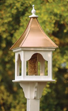 """American craftsmen make our handsome birdfeeder and birdhouse (Item #3029) of PVC board construction. Lift the bright copper roof to fill the Plexiglas tube with seed. The feeder measures 25"""" from the base of the mount to the top of the finial. Mount on a 4"""" x 4"""" pressure treated post (sold at home improvement centers). A vinyl sleeve is available to cover the post."""